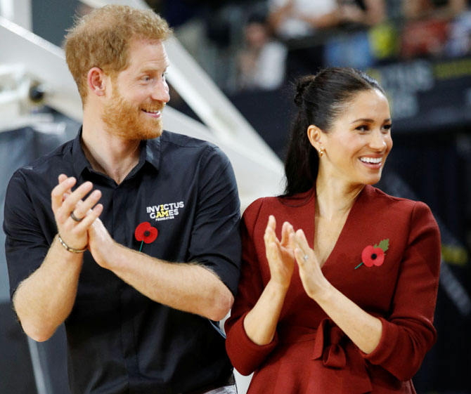 Britain's Prince Harry and Meghan, Duchess of Sussex, applaud before handing out awards to the Invictus Games Sydney 2018 wheelchair basketball medallists at Quaycentre in Sydney, Australia on Saturday