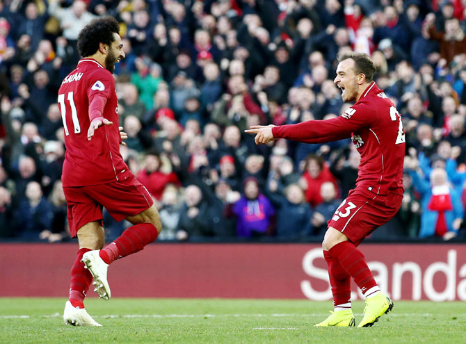 Liverpool's Xherdan Shaqiri celebrates with teammate Mohamed Salah after scoring his team's third goal against Cardiff City at Anfield in Liverpool on Saturday