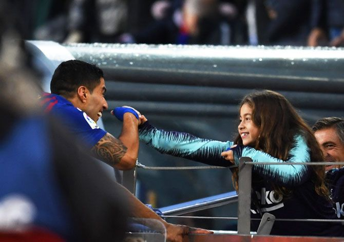Barcelona's Luis Suarez celebrates with his daughter after their La Liga EL Clasico victory over Real Madrid CF at Camp Nou in Barcelona on Sunday