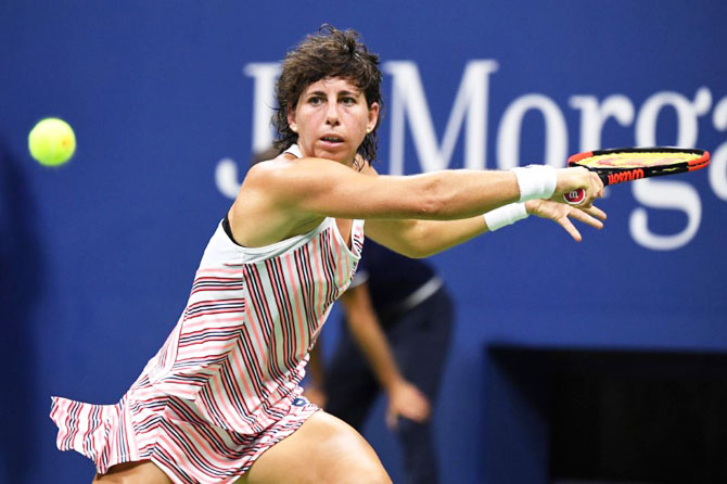 Spain's Carla Suarez Navarro returns a shot against Russia's Maria Sharapova