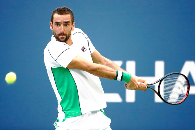Croatia's Marin Cilic returns the ball during the men's singles fourth round match against Belgium's David Goffin