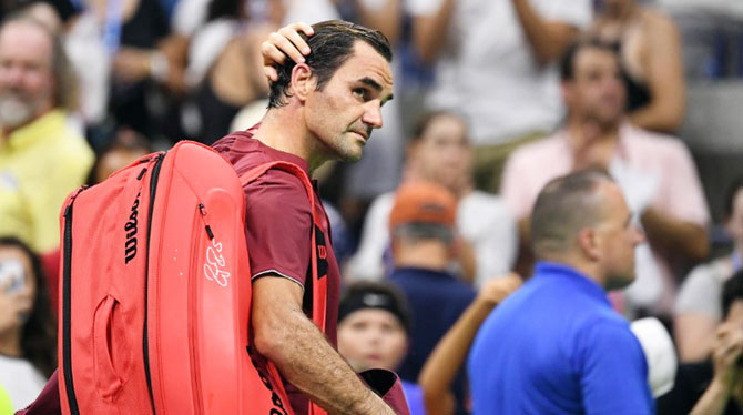 Switzerland's Roger Federer walks off the court after his loss to Australia's John Millman in their round of 16 match of the US Open on Monday