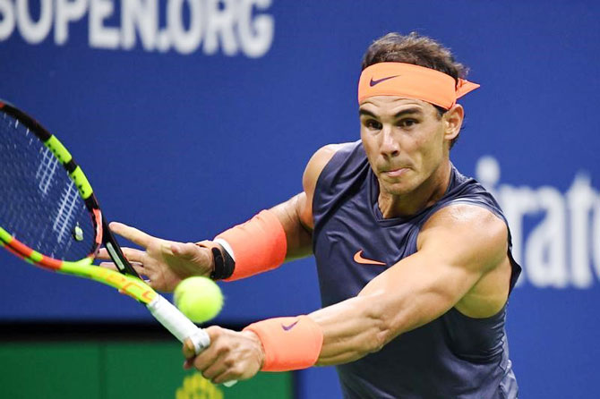 Rafael Nadal rushes to make a backhand return to Dominic Thiem