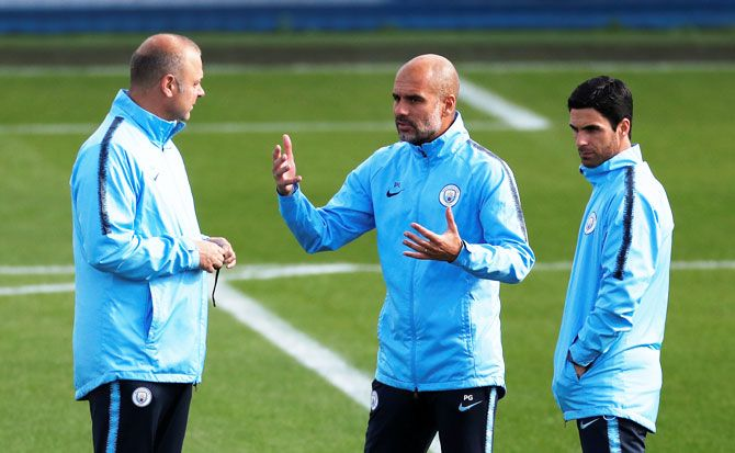 Manchester City manager Pep Guardiola (centre) with co-assistant coach Mikel Arteta (right) and Rodolfo Borrell during a training session