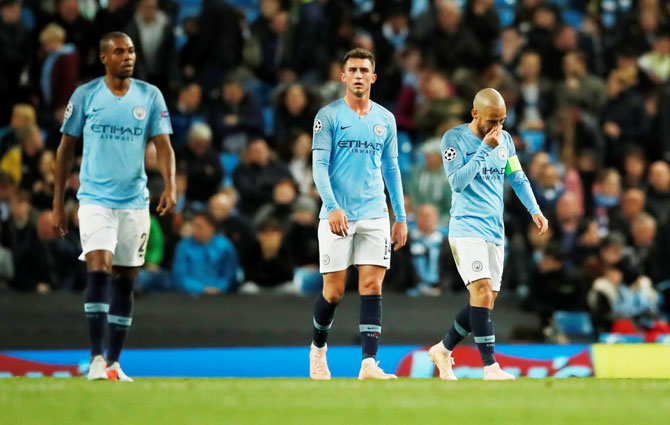 Manchester City's Fernandinho, Aymeric Laporte and David Silva look dejected after Lyon's second goal