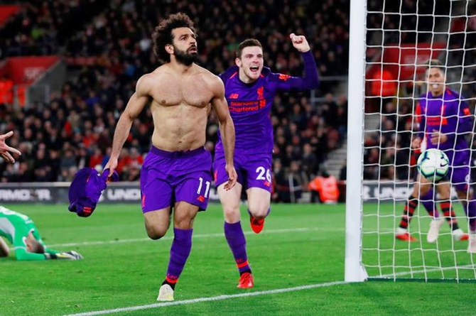 Liverpool's Mohamed Salah celebrates with teammate Andrew Robertson after scoring the second goal against Southampton during their English Premier League match, at St Mary's Stadium in Southampton on Friday, April 5.