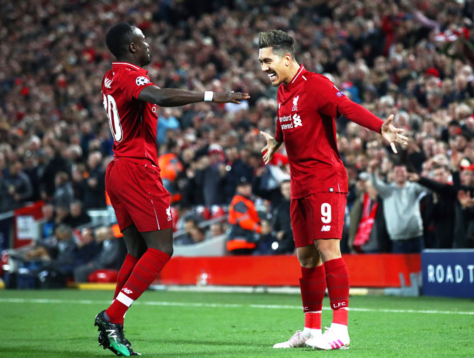 Liverpool FC's Roberto Firmino celebrates with teammate Sadio Mane after scoring the second goal against Porto during their UEFA Champions League quarter-final first leg match at Anfield in Liverpool, on Tuesday