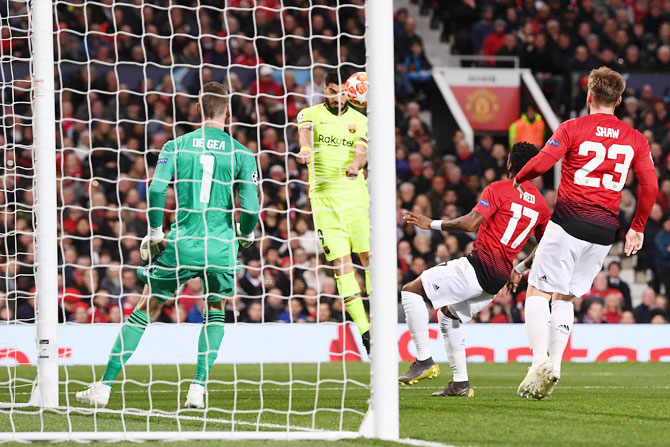 Barcelona's heads the ball that deflects off Manchester United's Luke Shaw (not in picture) for an own goal by Shaw during their match at Old Trafford in Manchester