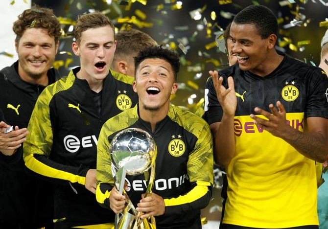 Jadon Sancho celebrates with the trophy after Borussia Dortmund beat Bayern Munich to win the German Super Cup.