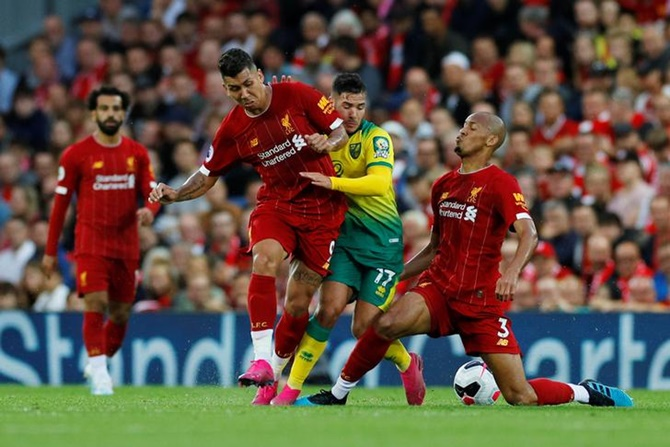Norwich City's Emiliano Buendia makes a strong challenge to stop Liverpool's Fabinho and Roberto Firmino.