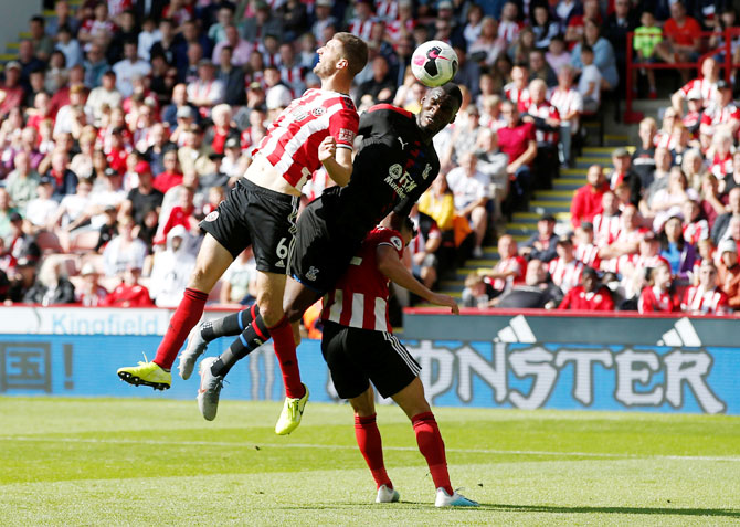 Crystal Palace's Christian Benteke is locked in an aerial battle with Sheffield United's Chris Basham and George Baldock