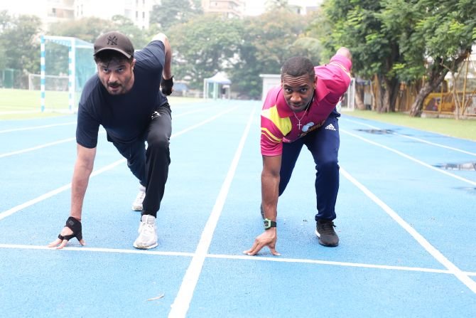 Veteran Bollywood star Anil Kapoor and Olympic silver medallist Yohan Blake warm up before a sprint in Mumbai on Thursday