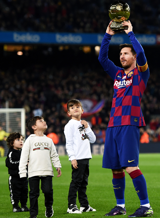 FC Barcelona's Lionel Messi presents his sixth Ballon d'Or trophy to the supporters as his children Ciro Messi Roccuzzo, Thiago Messi Roccuzzo and Mateo Messi Roccuzzo look on, before their La Liga match against Real Mallorca at Camp Nou in Barcelona on Saturday
