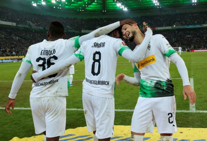 Borussia Moenchengladbach's Ramy Bensebaini celebrates with teammates after scoring their second goal against Bayern Munich at Borussia-Park in Moenchengladbach, Germany, on Saturday
