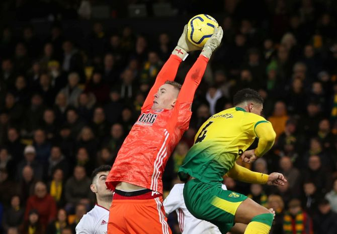 Sheffield United's Dean Henderson collects the ball as a Norwich City player takes evasive action during their match at Carrow Road in Norwich during their English Premier League match on Sunday, December 8