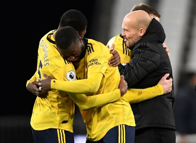 Arsenal's Ainsley Maitland-Niles and Nicolas Pepe celebrate alongside Arsenal interim manager Freddie Ljungberg after their win over West Ham at London Stadium in London on Monday