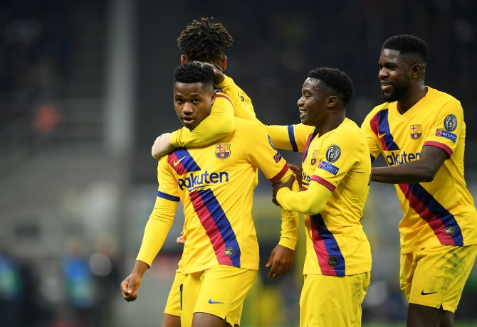 Barcelona's Anssumane Fati celebrates with teammates after scoring their second goal against Inter Milan at San Siro during their Champions League Group F match in Milan, Italy.