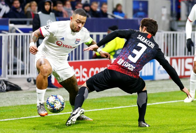 Olympique Lyonnais' Memphis Depay and with RB Leipzig's Marcelo Saracchi vie for possession during their Champions League Group G match at Groupama Stadium, Lyon, France