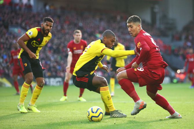 Liverpool's Roberto Firmino crosses the ball under pressure from Watford's Christian Kabasele