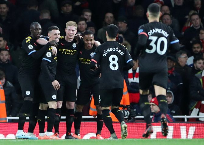 Manchester City's Kevin De Bruyne celebrates scoring their third goal with teammates during their EPL match against Arsenal at the Emirates Stadium in London