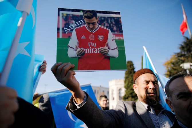 An ethnic Uighur demonstrator holds a placard with a picture of English soccer club Arsenal's midfielder Mesut Ozil during a protest against China in Istanbul, Turkey December 14, 2019