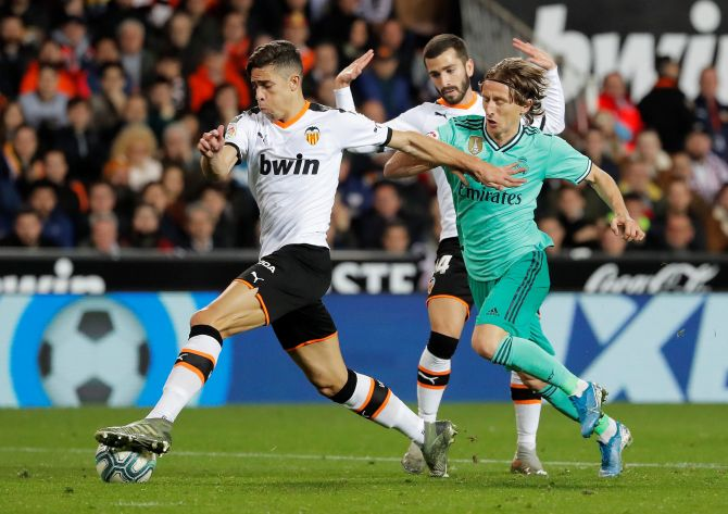 Real Madrid's Luka Modric staves off a challenge from Valencia's Gabriel Paulista as they battle for the ball