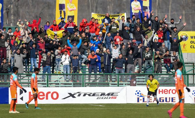 Supporters of Real Kashmir FC celebrate after their team's winning goal against Chennai City FC during their I-League match, in Srinagar on Thursday