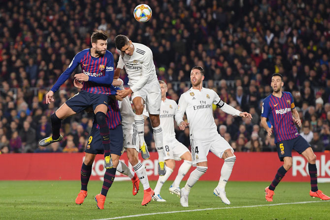FC Barcelona's Gerard Pique and Real Madrid's with Raphael Varane vie for the ball in an aerial battle for possession
