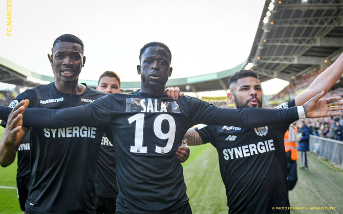 Nantes FC's Majeed Waris celebrates with teammates after scoring against Nimes on Saturday. The team wore an all black kit with the name of Sala on the back