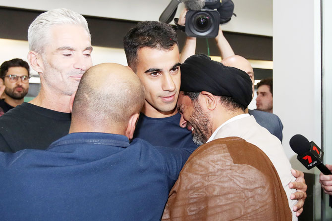 Hakeem al-Araibi receives an emotional welcome by a relative as he arrives in Melbourne with former Australian football captain and commentator Craig Foster at Melbourne Airport in Melbourne, Australia, on Tuesday, February 12. Bahraini refugee Hakeem al-Araibi was detained in November when he arrived in Thailand for his honeymoon, spending more than two months in jail while fighting extradition to Bahrain. Al-Araibi fled his home country in 2014 and was granted refugee status in Australia on the grounds he was persecuted and tortured in the Arabian Gulf state for participating in pro-democracy rallies