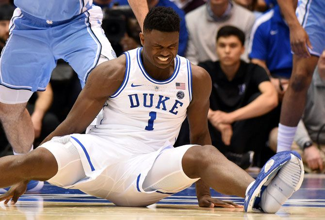 Duke Blue Devils forward Zion Williamson (1) reacts after falling as his shoe splits at the sole, during the first half against the North Carolina Tar Heels at Cameron Indoor Stadium on Wednesday, February 20