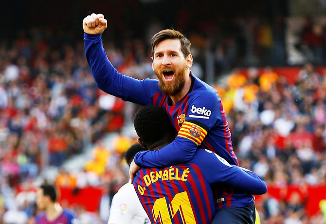 Barcelona's Lionel Messi celebrates scoring their second goal against Sevilla at Ramon Sanchez Pizjuan in Seville, Spain, on Saturday. He netted his 50th career hat-trick in the process