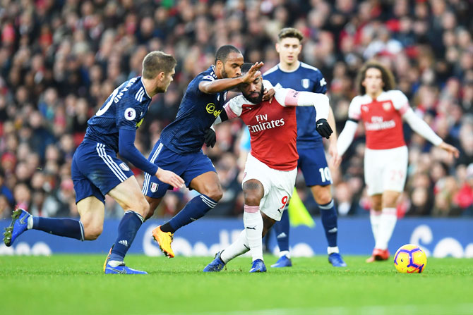 Arsenal's Alexandre Lacazette battles for possession with Fulham's Denis Odoi and Maxime Le Marchand during their match at Emirates Stadium