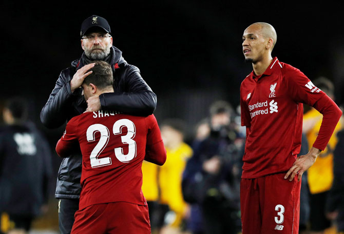 Liverpool manager Juergen Klopp consoles Xherdan Shaqiri as Fabinho looks on after being knocked out of the FA Cup by Wolverhampton Wanderers at Molineux Stadium, Wolverhampton, on Monday