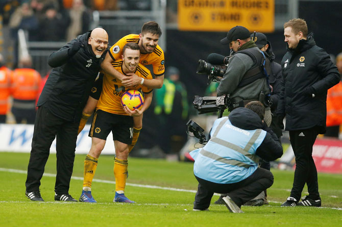 Wolverhampton Wanderers' Diogo Jota and Ruben Neves celebrate after the match against  Leicester City at Molineux Stadium, Wolverhampton