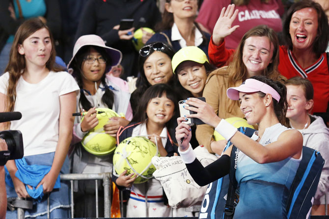 Spain's Garbine Muguruza takes a selfie for fans after her third round match against Switzerland's Timea Bacsinszky on Saturday