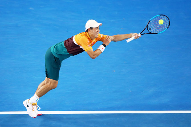 Japan's Kei Nishikori plays a backhand in his fourth round match against Spain's Pablo Carreno Busta