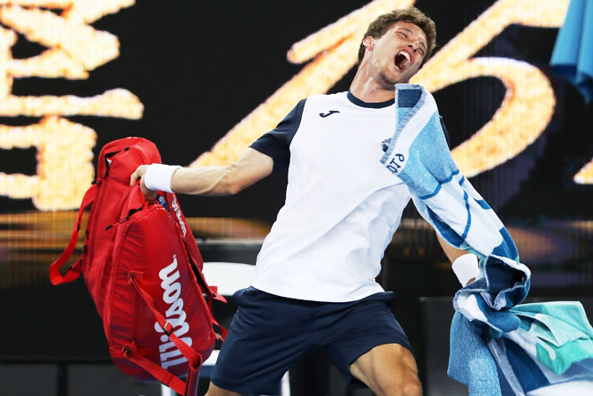 Spain's Pablo Carreno Bust throws his bag in frustration after losing his fourth round match against Japan's Kei Nishikori on Monday, January 21
