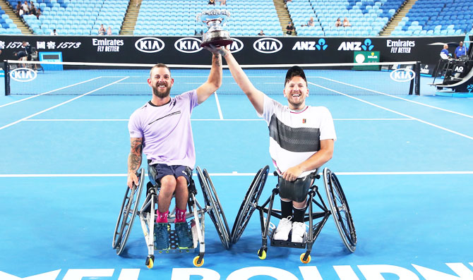 Australia's Dylan Alcott and Heath Davidson raise the cup after winning their Quad Wheelchair doubles final against Andy Lapthorne of Great Britain and David Wagner of the United States on Thursday, January 24