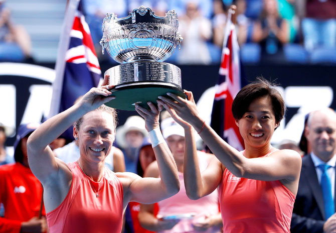 Australia's Samantha Stosur and China's Shuai Zhang celebrate with the trophy after winning the women's doubles final against Hungary's Timea Babos and France's Kristina Mladenovic on Friday
