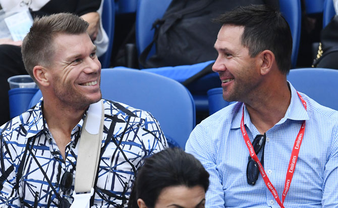 Banned Australian cricketer David Warner and former Australian cricket captain Ricky Ponting chat before the men's semi-final between Serbia's Novak Djokovic and France's Lucas Pouille on Friday