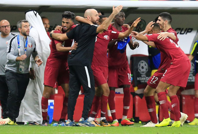 Qatar's Hamid Ismaeil celebrates with coach Felix Sanchez Bas and teammates after scoring their fourth goal against UAE on Tuesday