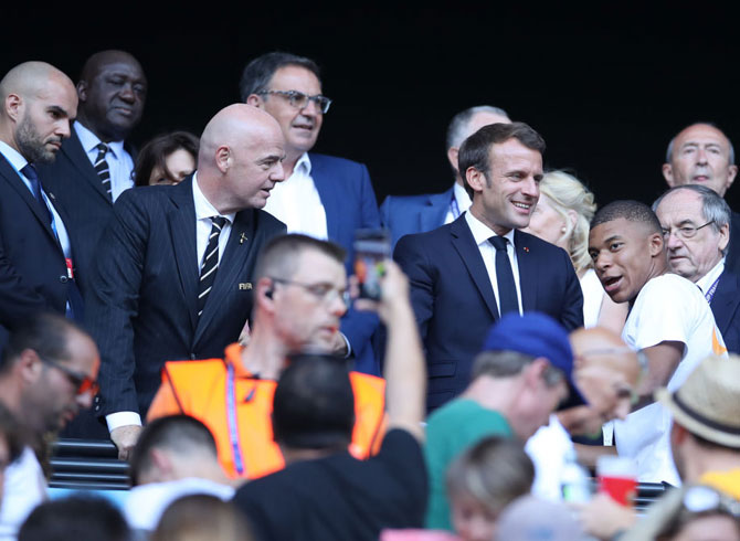 Emmanuel Macron, President of France, Gianni Infantino, FIFA President, and Kylian Mbappe, French footballer speak in the stands prior to the 2019 FIFA Women's World Cup in France between The United States of America and The Netherlands at Stade de Lyon in Lyon, France, on Sunday