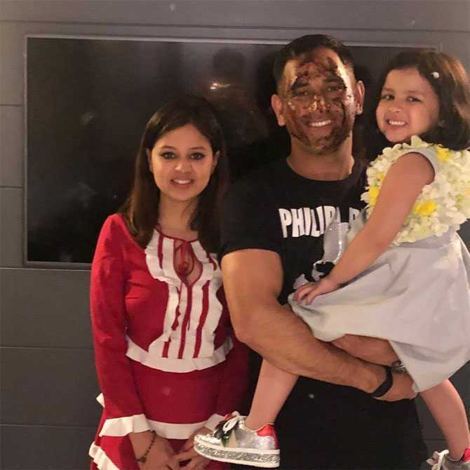 Mahendra Singh Dhoni, his face smudged with cake, poses with his wife Sakshi and daughter Ziva during his birthday celebrations on Saturday