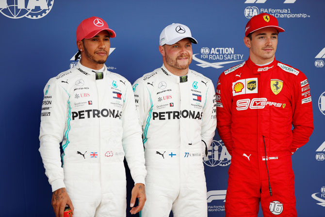 Mercedes' Lewis Hamilton who qualified in second position, Mercedes' Valtteri Bottas who qualified in pole position and Ferrari's Charles Leclerc who qualified in third position pose for a photo on the podium after qualifications for the British Grand Prix at the Silverstone Circuit, Silverstone, Britain on Saturday