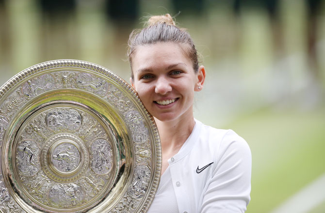 Romania's Simona Halep celebrates with the trophy after winning the Wimbledon final against USA's Serena Williams on Saturday