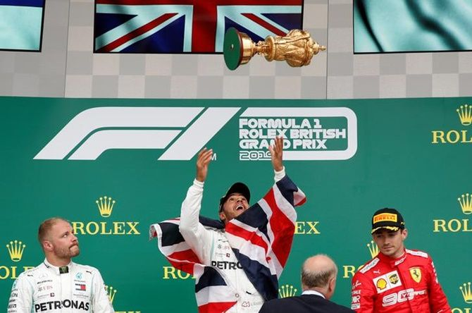 Lewis Hamilton throws the trophy in the air as he celebrates winning the race on the podium, alongside Mercedes's Valtteri Bottas, who finished second, and Ferrari's Charles Leclerc, who finished third.