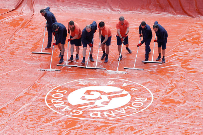 Grounds staff clean the court during the men's semi-final betweeen Serbia's Novak Djokovic and Austria's Dominic Thiem at Roland Garros in Paris on Saturday