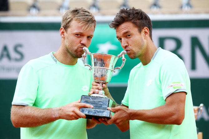 Germany's Kevin Krawietz and Andreas Mies kiss the trophy as they celebrate winning the French Open men's doubles final against France's Jeremy Chardy Fabrice Martin at Roland Garros on Saturday