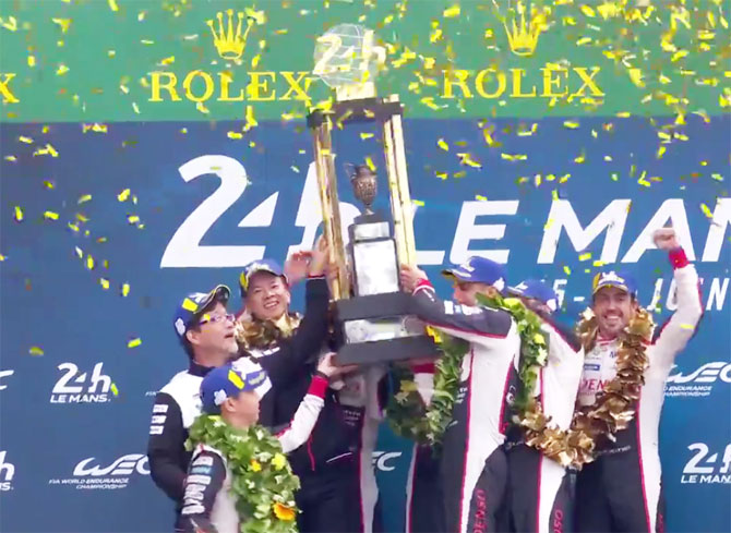 Fernando Alonso (extreme right) celebrates on the podium with his Toyota team mates Kazuki Nakajima and Switzerland's Sebastien Buemi after winning the Le Mans 24 Hours sportscar race on Sunday